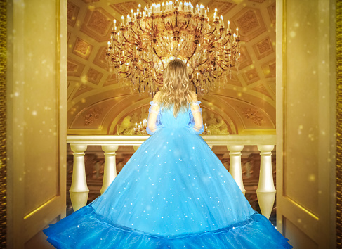 Beautiful princess in blue long shiny dress on the luminous yellow chandelier background