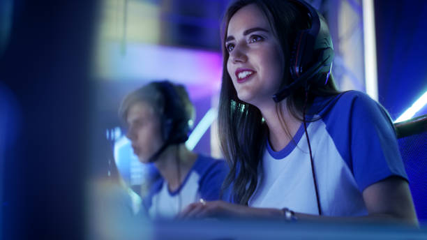 beautiful professional gamer girl and her team participate in esport cyber games tournament. she has her headphones and as a team leader she commands strategical maneuvers into microphone. - esports stock photos and pictures