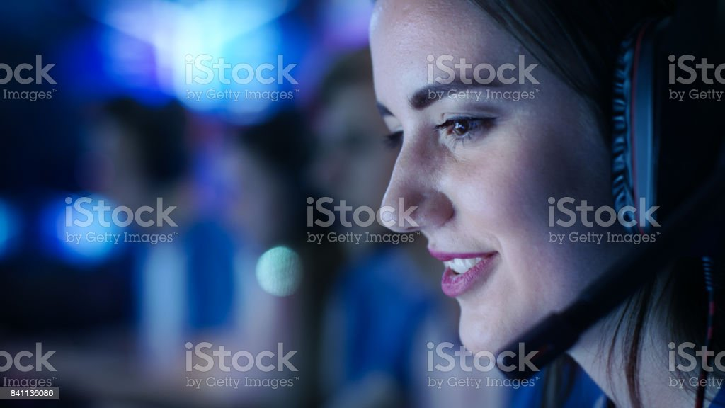 Beautiful Professional Gamer Girl and Her Team Participate in eSport Cyber Games Tournament. She Has Her Headphones and Talks into Microphone. stock photo
