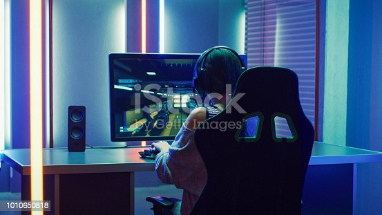 istock Beautiful Professional Gamer Girl Playing in First-Person Shooter Online Video Game on Her Personal Computer. Casual Cute Geek Girl Wearing Headset. Dark Room Suddenly Lit by Neon Lights in Retro Arcade Style. 1010650818