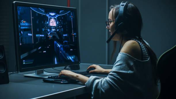 Schöne professionelle Gamer Mädchen in First-Person-Shooter Online-Video-Spiel auf ihrem PC spielen. Lässige niedlich Geek Mädchen tragen Kopfhörer. In den unterirdischen Spielverein. – Foto