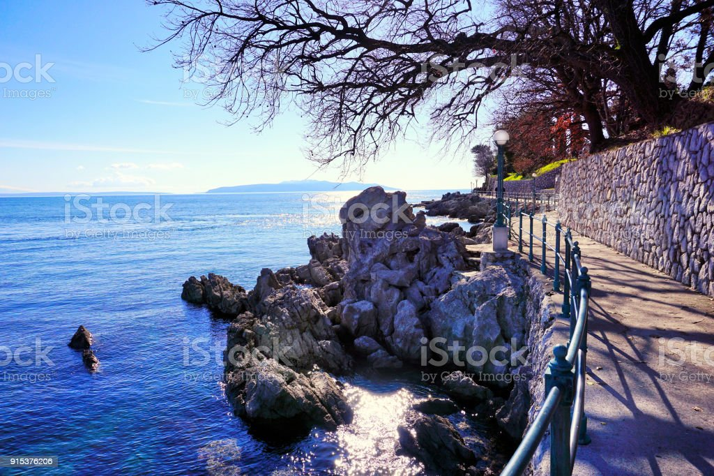 Beautiful promenade by the clear blue sea in the winter sunny day stock photo