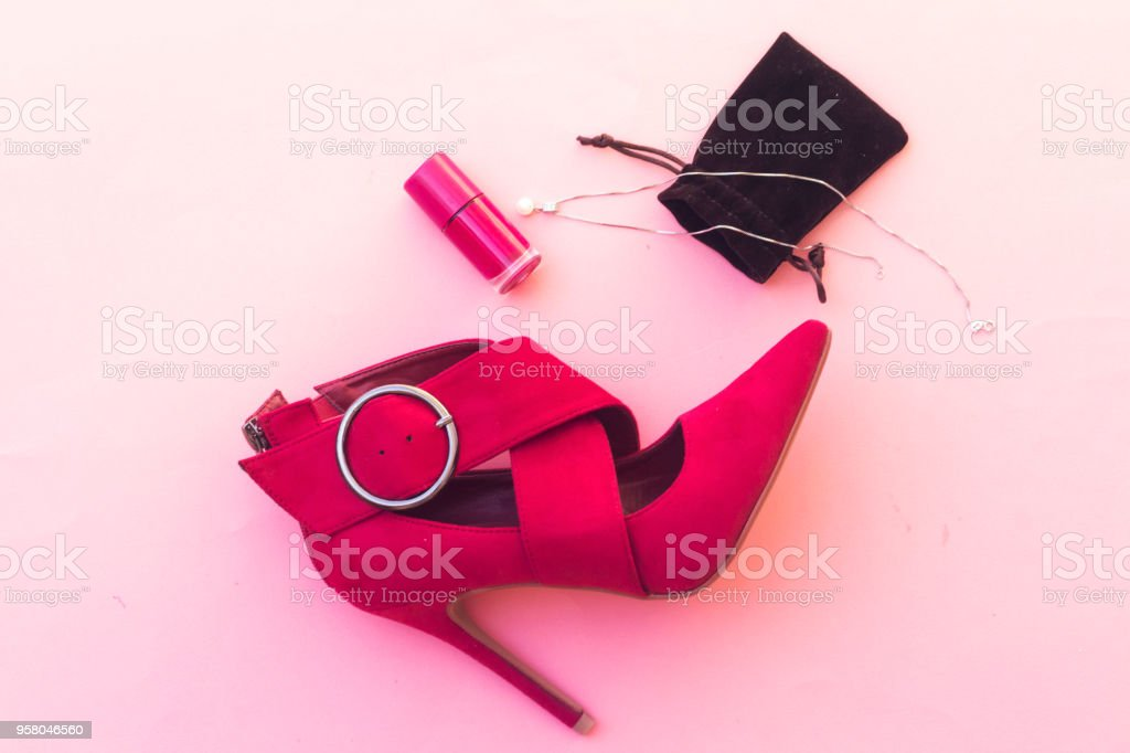 beautiful pump hight heeled and pink nail polish bottle and white pearl necklace stock photo
