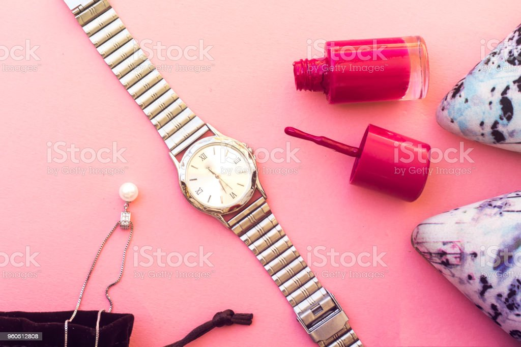 beautiful  pump hight heeled and pink nail polish bottle and white pearl necklace and silver watch stock photo