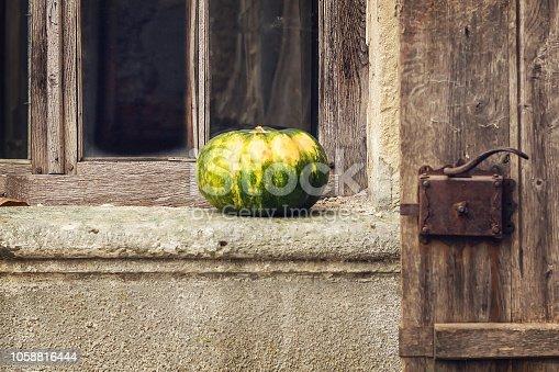 istock Beautiful pumpkin on the windowsill on the background of the old window. 1058816444