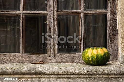 istock Beautiful pumpkin on the windowsill on the background of the old window. 1058816578