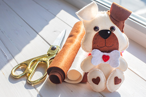 A beautiful puppy made of felt with a brown ear and muzzle, with a bone and a red heart sits on a background of white boards. Tailor's scissors, felt rolls. Creativity, hobby, sewing toys with a child