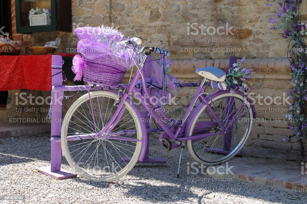 Beautiful purple bicycle with large decorative basket of lavender flowers in front of it stock photo