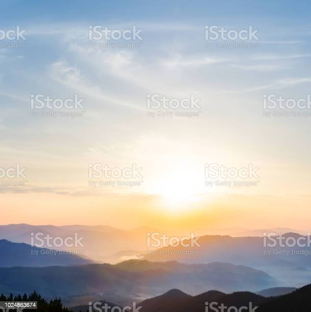 Photo of beautiful quiet sunset among the mountain valley with blue mist