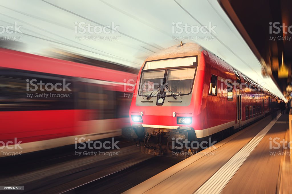 Beautiful railway station with modern red commuter train at sunset stock photo
