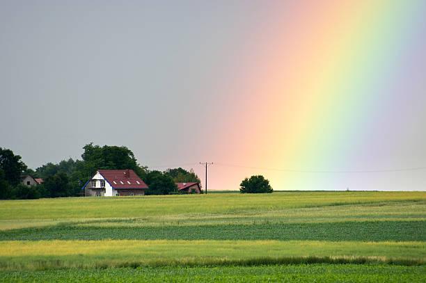 Beautiful rainbow over the village stock photo