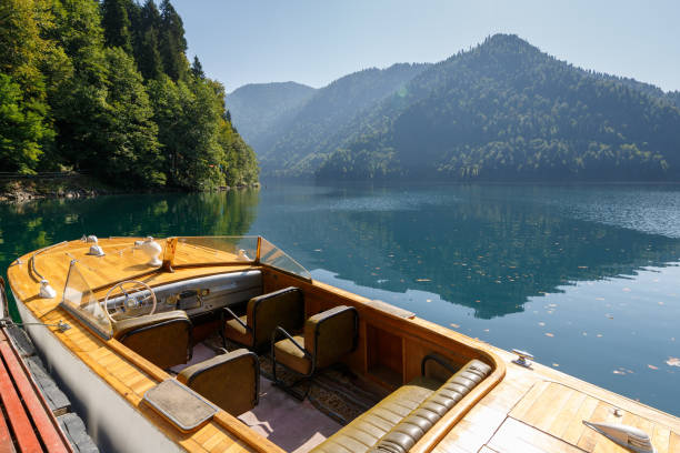 Beautiful rarity wooden speed boat on the background of the mountains on Lake Ritsa stock photo
