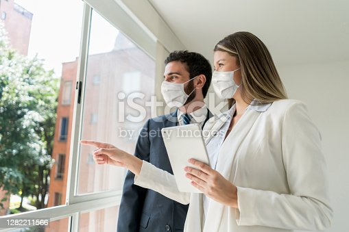 Beautiful real estate agent pointing at the view to customer both looking very cheerful but wearing protective face masks - Coronavirus concepts