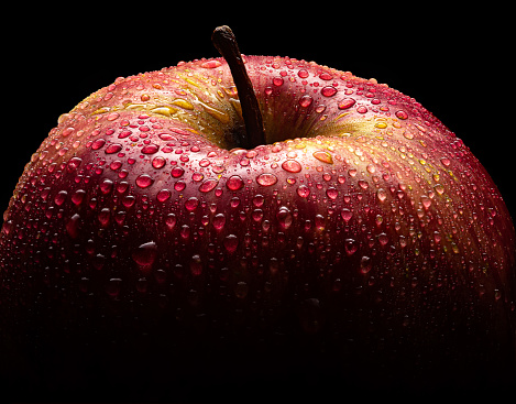 Beautiful red Apple on black background closeup macro with lots of water droplets