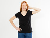 istock Beautiful red hair girl in a black t-shirt isolated on white. Pretty smile red head woman in tshirt mock up blank. 1245066652