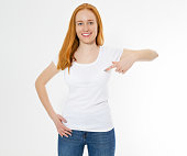 istock Beautiful red hair girl pointed on a white t-shirt isolated. Pretty smile red head woman in tshirt mock up, blank. 1219981485