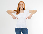 istock Beautiful red hair girl pointed on a white t-shirt isolated. Pretty smile red head woman in tshirt mock up, blank. 1223843851