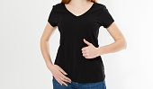 istock Beautiful red hair girl show like sign on a black t-shirt isolated. Pretty smile red head woman in tshirt mock up, blank. 1253498352