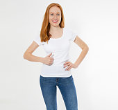 istock Beautiful red hair girl show like sign on a white t-shirt isolated. Pretty smile red head woman in tshirt mock up, blank. 1221837233