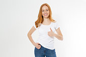 istock Beautiful red hair girl show like sign on a white t-shirt isolated. Pretty smile red head woman in tshirt mock up, blank. 1245066655