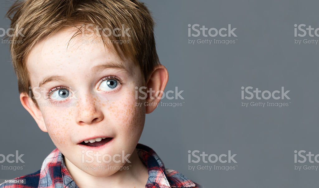beautiful red hair preschooler with freckles looking up to daydream stock photo
