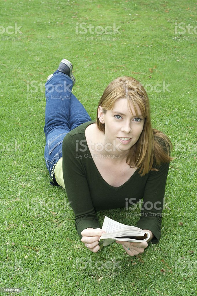 Beautiful Red Haired Girl Reading on the Grass royalty-free stock photo