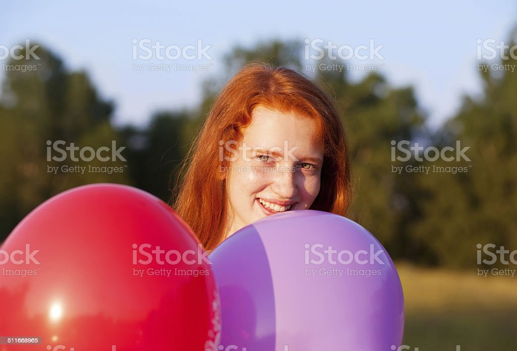 Beautiful red haired teenager girl with balloons, outdoors, smil stock photo