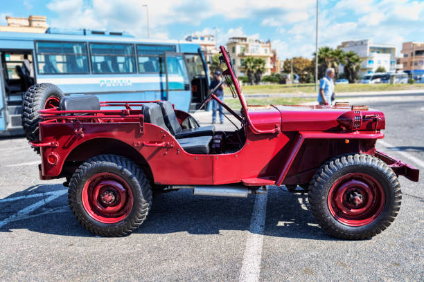 A beautiful red Jeep Willys MB used in the Celere Department of the Italian Police in the post-war period Rome,Italy - September 30, 2018: The 50th anniversary of the foundation of the National Association of State Police, outdoor exhibition with vintage cars with historical Jeep Willys MB  used in the Celere Department of the Italian Police in the post-war period. willys stock pictures, royalty-free photos & images