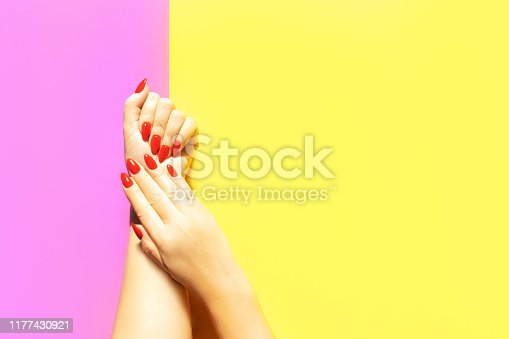 1128559926 istock photo Beautiful red manicure in the hands of a young woman. 1177430921
