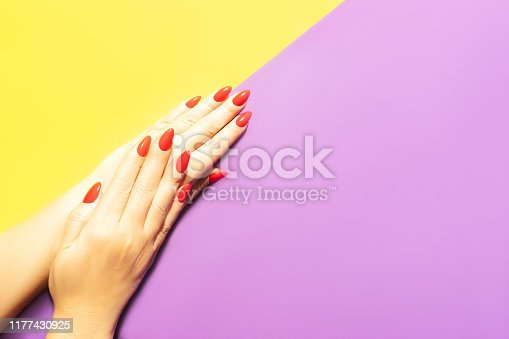 1128559926 istock photo Beautiful red manicure in the hands of a young woman. 1177430925