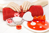 beautiful red manicure with red orchid flower and towel on the white wooden table.
