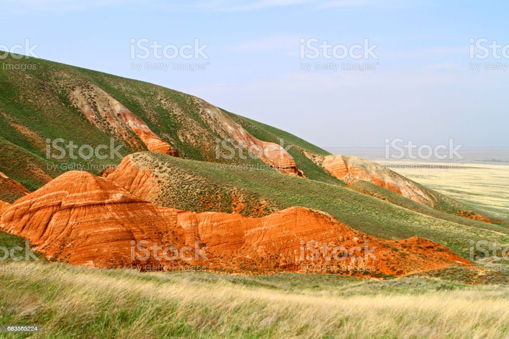Beautiful red mountains with the green grassy slope in steppe stock photo