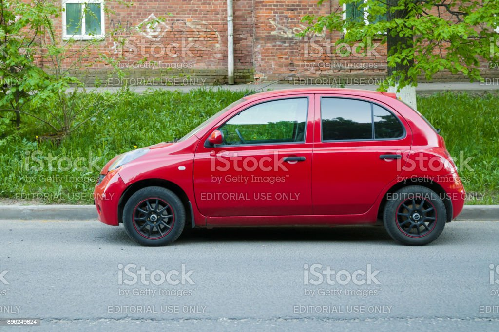 Beautiful red Nissan Micra (March) parked on the street. stock photo