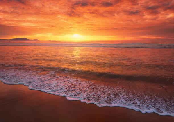 hermosa puesta de sol roja en la playa con una ola en la orilla - foto de stock
