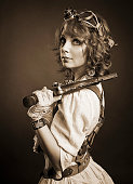 istock Beautiful redhair steampunk girl with gun looking at camera. Old 538390741