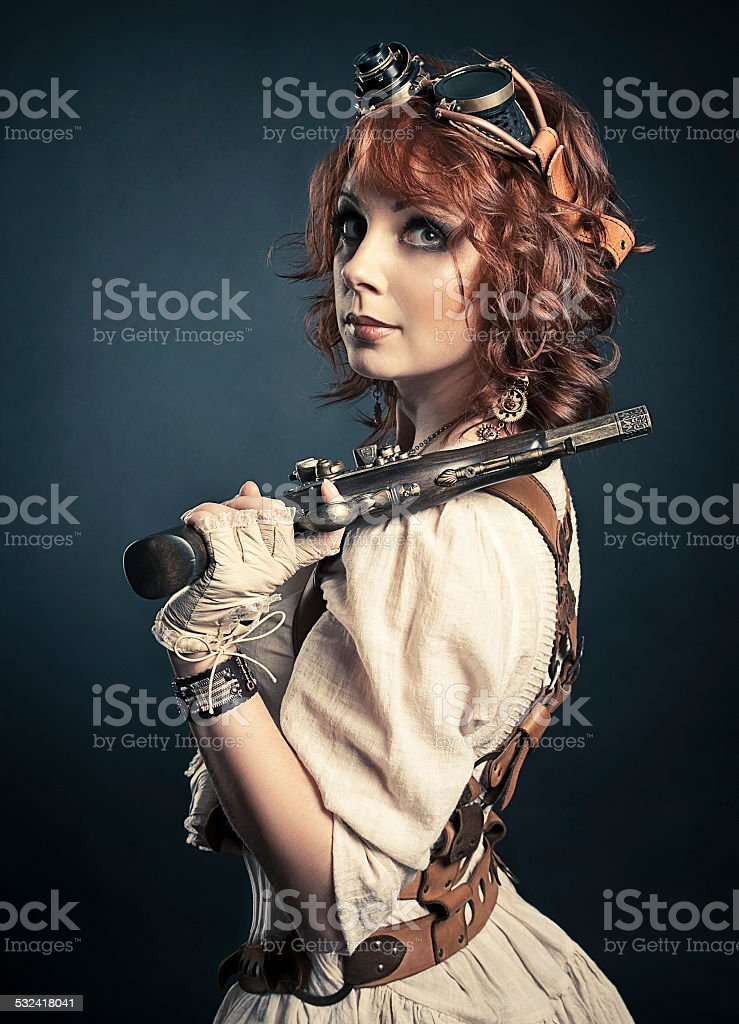 Beautiful redhair steampunk girl with gun looking at camera stock photo