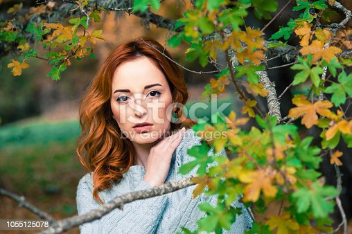 Young cute girl with red hair, posing behind a branch.
