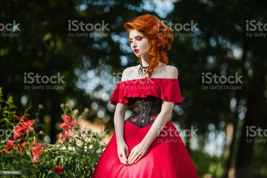 Beautiful Redhaired Girl In A Red Dress And In Black Corset On A