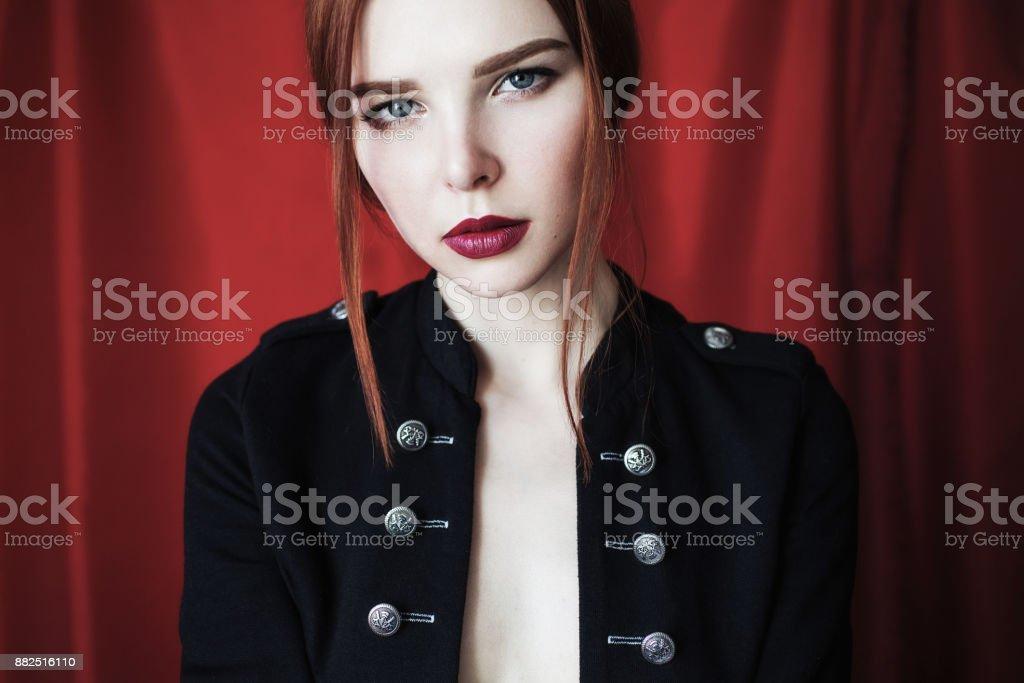 e5ecb0953 Hermosa chica pelirroja en chaqueta desabrochada negra con labios rojos  sobre fondo rojo mirando a la