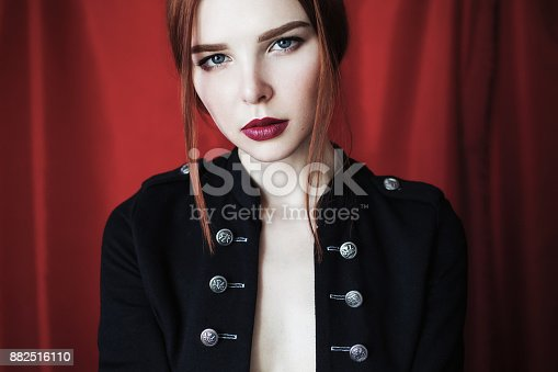d5efa3629a8161 882516110istock Hermosa chica pelirroja en chaqueta desabrochada negra con  labios rojos sobre fondo rojo mirando a