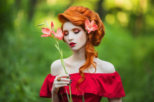 schöne rothaarige mädchen im roten kleid posiert auf grünem hintergrund. porträt einer frau mit roten haaren in einem sommer wald mit blume - prinzessinnenstil stock-fotos und bilder