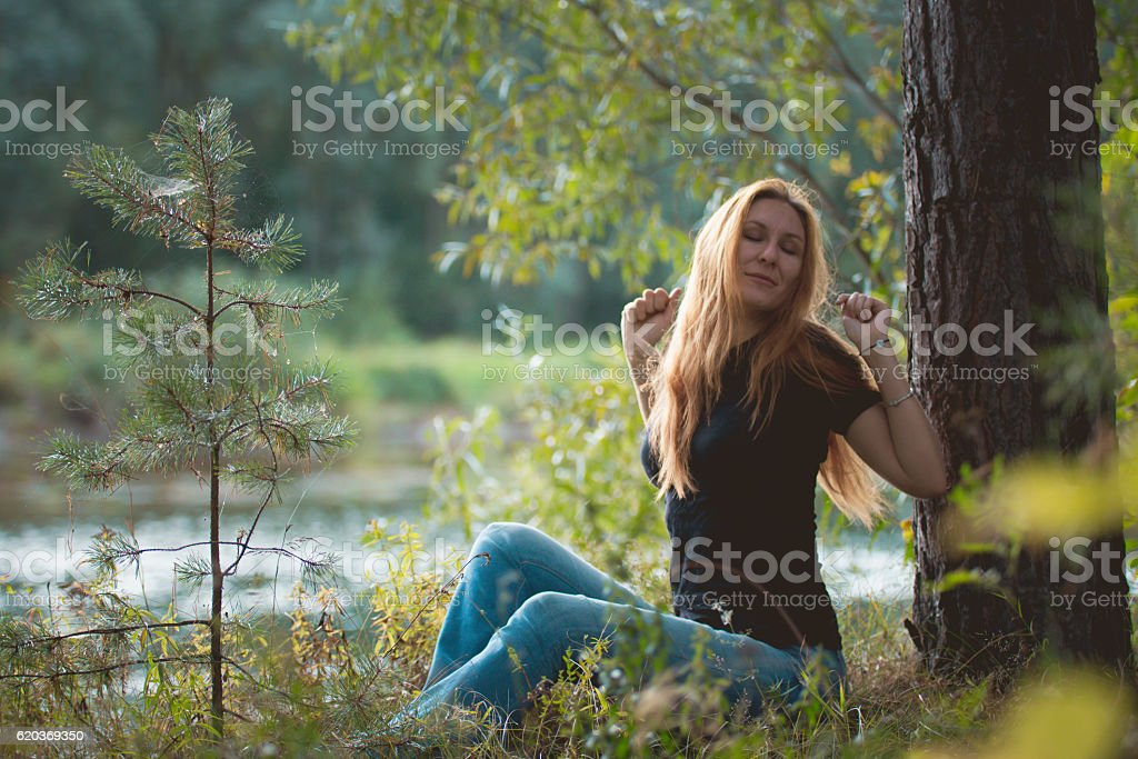 Beautiful red-haired girl sitting near river at forest and zbiór zdjęć royalty-free