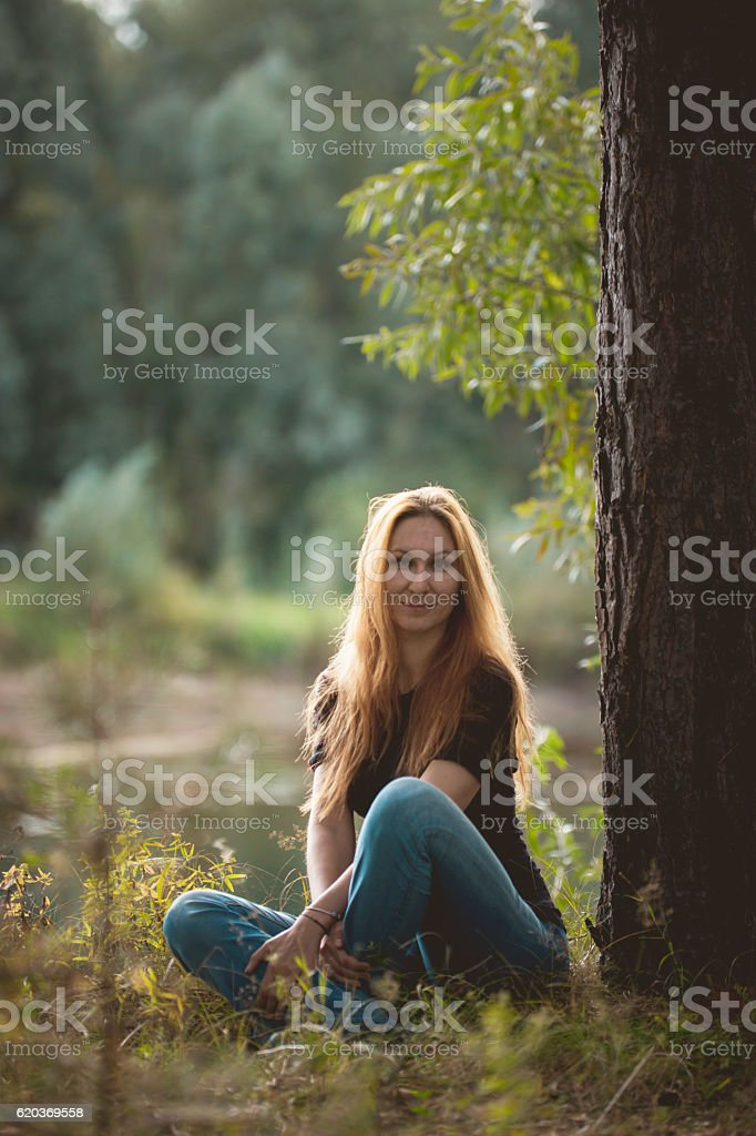 Beautiful red-haired girl sitting near river at forest and foto de stock royalty-free
