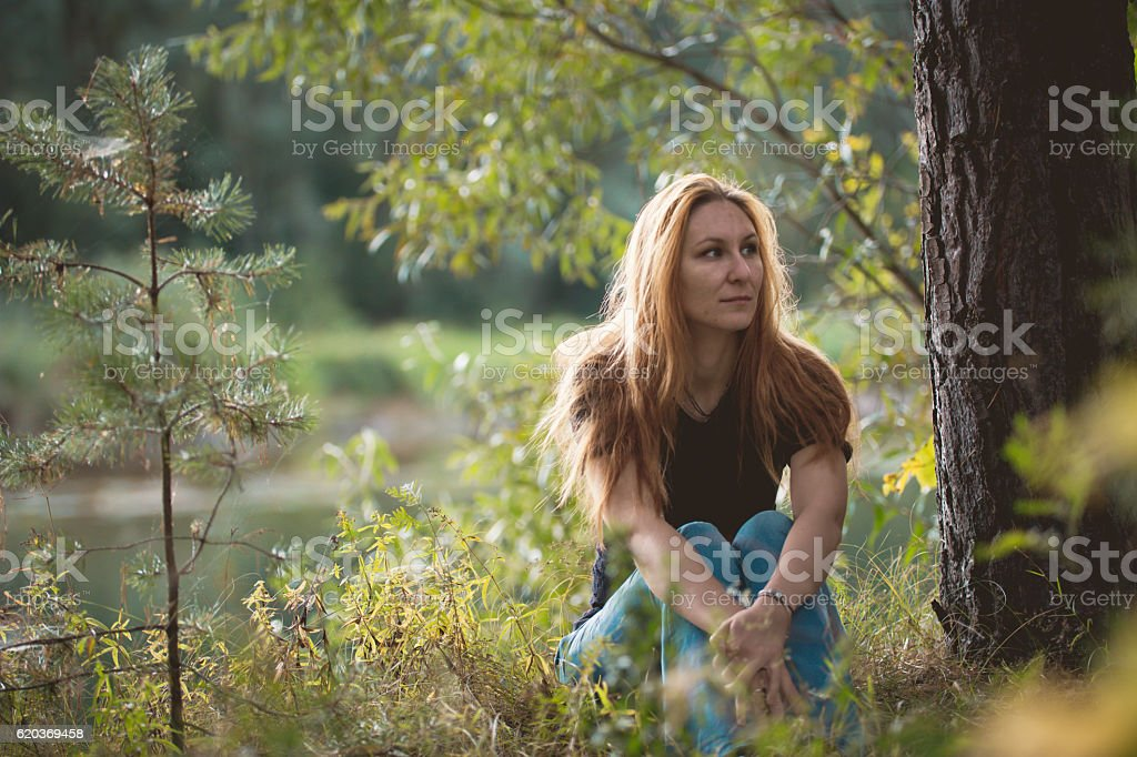 Beautiful red-haired girl sitting near river at forest zbiór zdjęć royalty-free