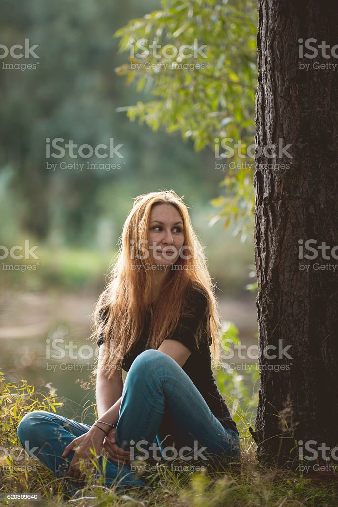 Beautiful red-haired girl sitting near river at forest, vertical zbiór zdjęć royalty-free
