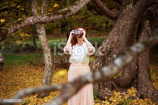 Young woman with long red hair and retro style camera, dressing vintage clothes, takes photos in a autumn scenario.