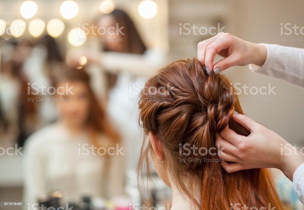 漂亮的紅發女孩留著長頭髮,理髮師編織法國的辮子,在一家美容院 - 免版稅人圖庫照片