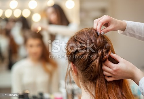 istock Beautiful, red-haired girl with long hair, hairdresser weaves a French braid, in a beauty salon 671018482