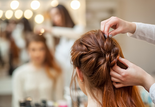 漂亮的紅發女孩留著長頭髮理髮師編織法國的辮子在一家美容院 照片檔及更多 人 照片