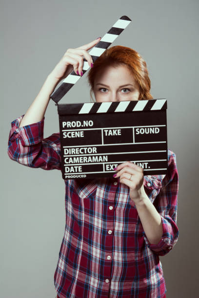 Beautiful red-haired woman holding a movie clapper, isolated over gray background. stock photo